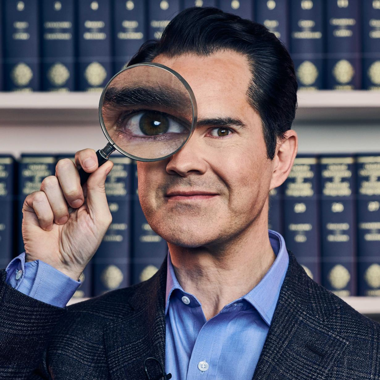 Jimmy Carr looking through a magnifying glass.