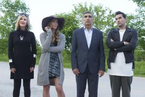 Pictured: The Rose family - Moira (Catherine O'Hara), Alexis (Annie Murphy), Johnny (Eugene Levy), and David (Dan Levy) - look at the Schitt's Creek town sign